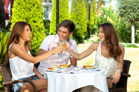 lifestyle dining: Three friends celebrating seated at an outdoor table in the garden toasting each other with champagne and enjoying a healthy tropical fruit meal