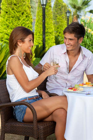 courting: Young couple in love toasting while having lunch outdoors in a warm day
