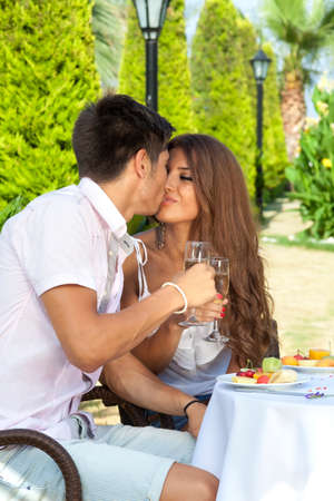 Young beautiful couple kissing while having a fancy lunch outside in a warm sunny day photo