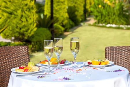 Viering voor drie met een restaurant tafel met uitzicht op een tuin voor drie met hapjes van vers gesneden tropisch fruit en fluiten van champagne