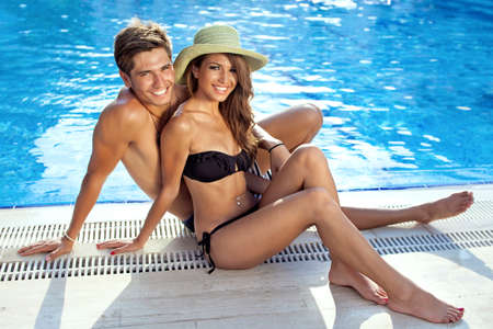 Happy beautiful young couple sitting at the edge of the swimming pool, in a hot sunny day