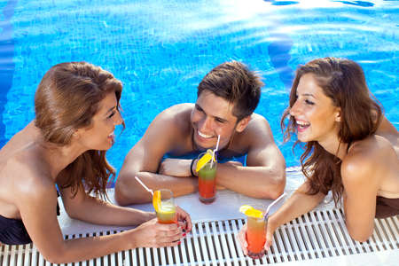 Good looking guy flirting with two women at the swimming pool, drinking cocktails Stock Photo
