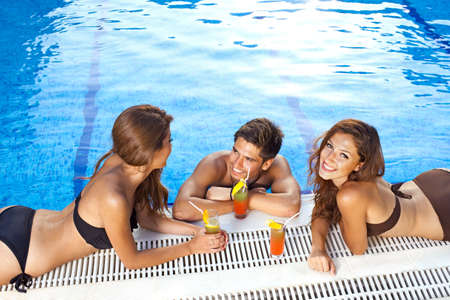 bikini pool: Handsome young man standing in a sparkling blue swimming pool chatting to two beautiful women in bikinis sunbathing on the edge