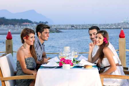 Twee aantrekkelijke jonge koppels vieren op een restaurant aan zee zitten aan een tafel aan de waterkant te wachten op hun maaltijd en genieten van een glas wijn
