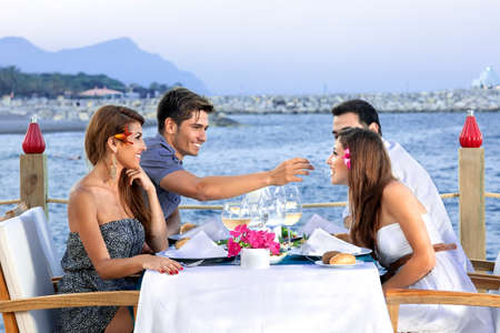Two couples celebrating at the sea seated at a table at an open-air waterfront restaurant enjoying glasses of cold white wine as they wait for their meal Stockfoto