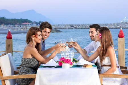 Groep van vier vrienden vieren in een restaurant aan zee zittend aan tafel opvoeding van hun wijnglazen in een toast met de oceaan en een stedelijke kustlijn in de achtergrond