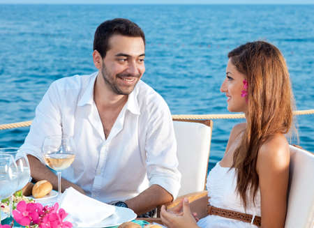 Young couple enjoying a romantic meal sitting at a table at a waterfront restaurant talking to each other with an ocean backdrop Stock Photo