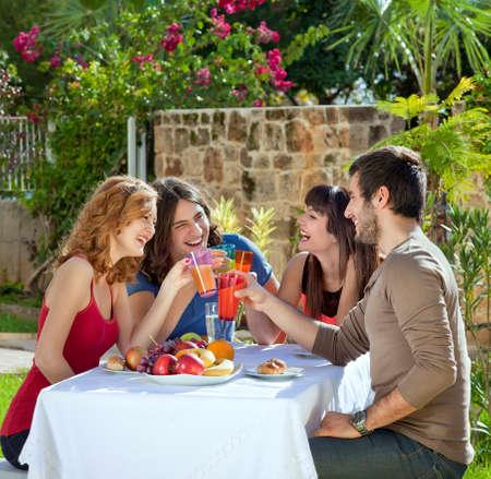 Koppels genieten van een gezonde lunch buiten in de tuin lachen en grappen maken als ze elkaar proosten met hun drankjes