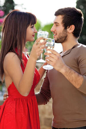 Romantic young couple dancing with glasses of white wine in their hands as they stare into each others eyes with a smile photo