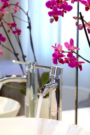 handbasin: Clear fresh water running out of a stainless steel tap into a white basin overhung with orchids reflected in a mirror Stock Photo