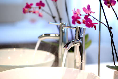 therapeutical: Clear fresh water running out of a stainless steel tap into a white basin overhung with orchids reflected in a mirror Stock Photo
