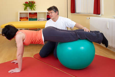 adult practicing poses on exercise ball with professional