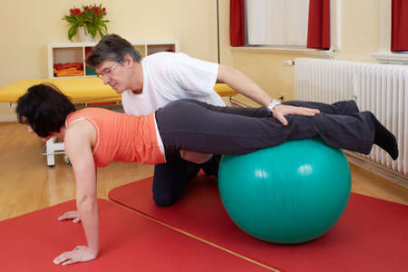 therapeutical: adult practicing poses on exercise ball with professional