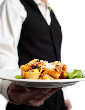 A servant is holding a plate with pasta, tomato sauce, parmesan and basil.€ Focus on plate. Close-up.