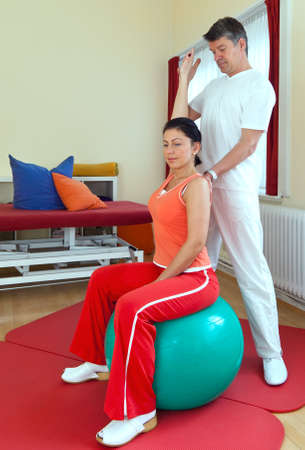 therapeutical: Physiotherapist standing behind a woman seated on a medical or pilates ball extending her arm and bending it backwards to maintain flexibility and movement in the shoulder Stock Photo