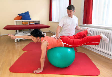 physio: adult practicing poses on exercise ball with professional