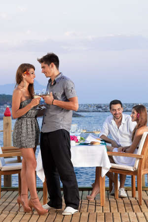 boat party: Young romantic couple standing close together on a wooden deck overlooking the sea drinking white wine
