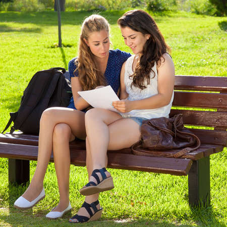 Students going over homework  Two girls are going over homework at a park photo