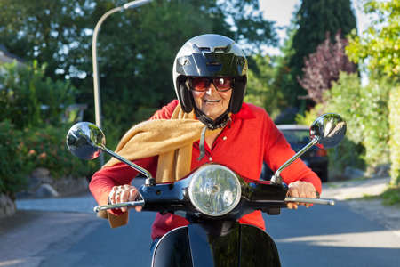 Senior lady wearing a helmet, sunglasses and a scarf riding her scooter directly at the camera with a wide smile of pleasure