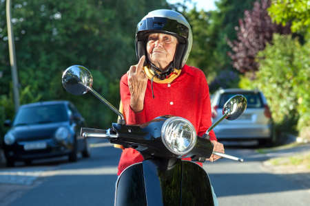 supercilious: Senior woman showing the finger while sitting on a scooter bike in a sign of road rage Stock Photo