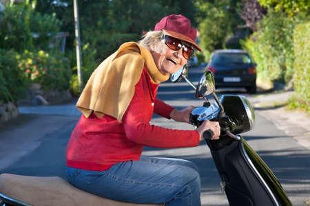 뾰족한 모자, 스카프, 선글라스를 착용하고있는 스쿠터를 타는 삶에 대한 열정을 지닌 유행하는 고위 여성 웃음