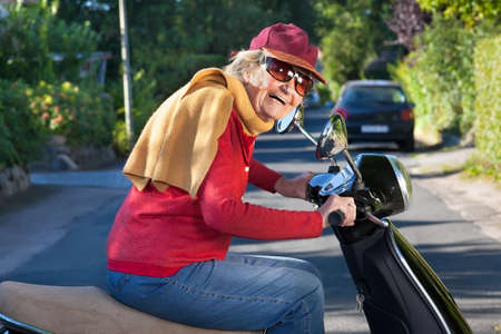 zest for life: Laughing trendy senior woman with a zest for life riding along on her scooter wearing a peaked cap, scarf and sunglasses