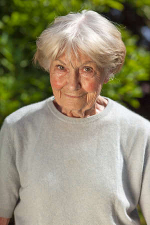 Kindly elderly lady standing in her garden looking at the camera with a friendly smile photo
