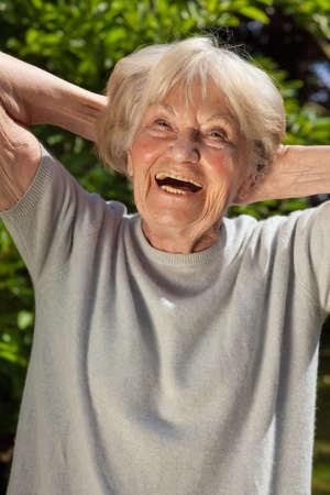 Senior dame met een goed gevoel voor humor met een hartelijke lach als ze geniet van de zon buiten in haar tuin op een zomerse dag