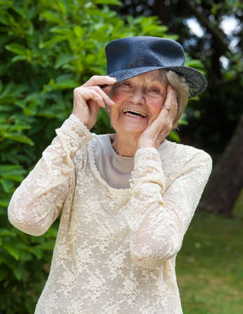 brim: Portrait of a lively laughing elderly lady wearing a hat lifting her hand to the brim as she stands outdoors in a lush green garden or park
