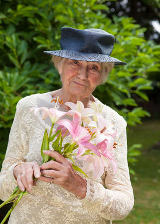 bygone: Senior lady holding a bouquet of fresh lilies as she stands in her green garden with a wistful look of nostalgia as she recalls bygone memories