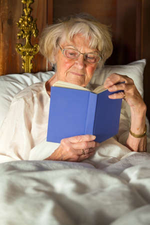 pleasure of reading: Elderly woman in her nightgown wearing glasses sitting propped up against the pillows reading a hardcover book in bed Stock Photo