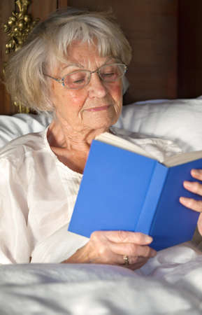 pleasure of reading: Elderly female pensioner wearing glasses reading a book in bed sitting propped up comfortably against her pillows