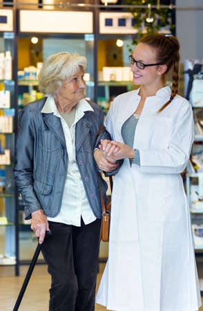 Young female pharmacist gently holding and supporting senior female patient in the pharmacy Stock Photo