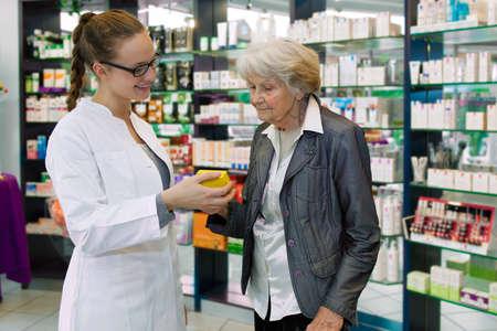 drugstore: Farmacéutico joven que da consejos sobre medicamentos para paciente de alto nivel en una farmacia Foto de archivo