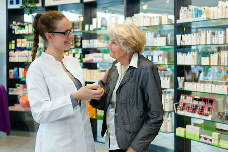 Pharmacist helping a grateful senior patient woman in the pharmacy