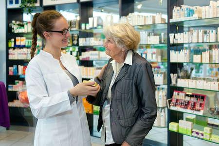 Apotheker het helpen van een dankbare patiënt senior vrouw in de apotheek