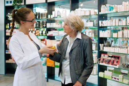 Apotheker helpen een dankbare senior patiënt vrouw in de apotheek