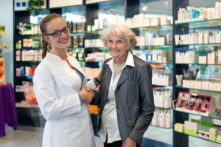 Senior dame met een mooie glimlach handen schudden met een mooie jonge vrouwelijke apotheker als ze staan samen in de apotheek de bespreking van de producten en medicatie