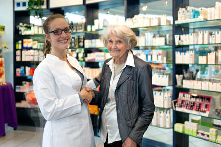 assisting: Smiling friendly female pharmacist wearing glasses assisting an elderly lady in her pharmacy or drugstore shaking hands with a lovely smile