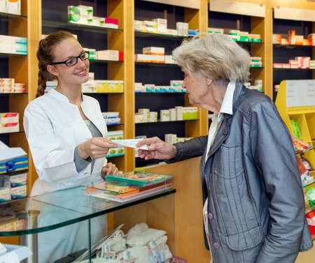 Glimlachend aantrekkelijke jonge vrouwelijke apotheker waar een senior dame over de toonbank verstrekking haar voorgeschreven medicatie
