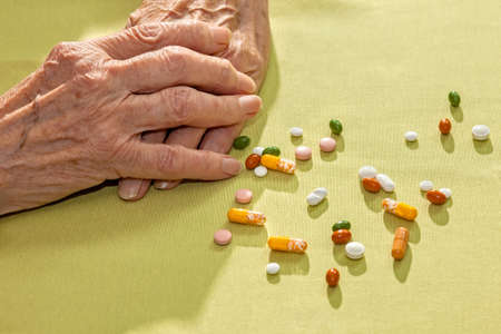 arthritic: Clasped hands of an elderly lady resting on a table alongside a variety of scattered medication, tablets capsule and pills, prescribed for her health and as diet supplements