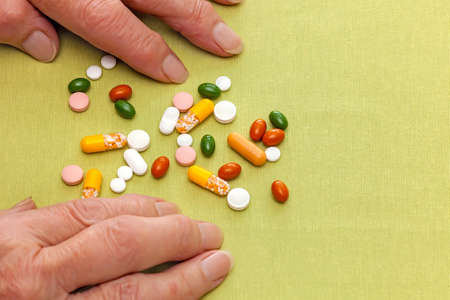 Close up of the hands of an old woman confused by her medication on either side of a scattered pile of tablets, pills, and capsules on a table, with copyspace