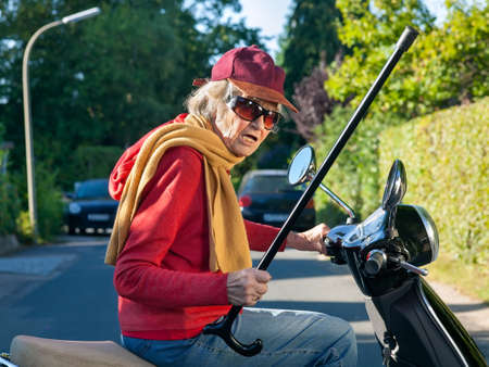 brandishing: Senior lady in a trendy cap, sunglasses and scarf riding on a scooter waving her cane with a threatening gesture as she passes down the road Stock Photo