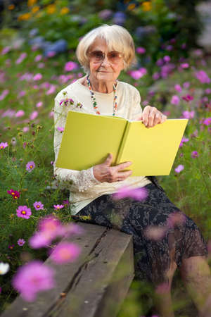 Elderly stylish woman wearing sunglasses sitting in her garden on a wooden bench amongst the flowers with a book enjoying the summer sun photo