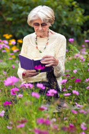 Senior woman sitting reading a book amongst the beautiful fresh summer flowers in her garden enjoying the tranquillity of nature photo