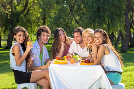 Group of happy vivacious teenagers full of vitality enjoy a fruity meal together sitting around a picnic table outdoors in the park