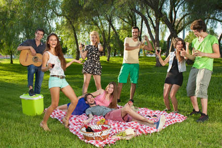 picnicking: Group of happy lively teenage friends dancing to guitar music as they spend a relaxing day picnicking and relaxing in the park on a summer day during their vacation