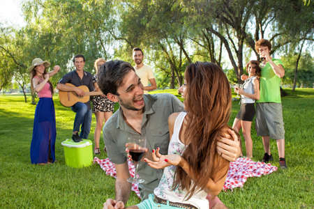 Happy romantic young teenage couple in an affectionate embrace enjoying a good laugh together in the park watched by a group of their college friends as they relax on their summer vacation photo