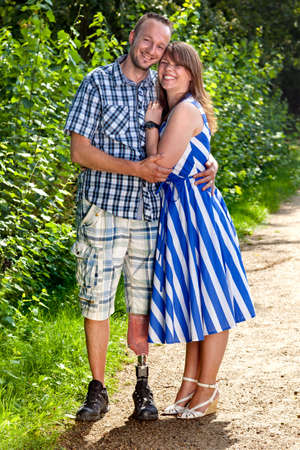 Confident attractive smiling young couple in a loving embrace standing outdoors on a gravel path - the man is a handicapped amputee wearing a prosthetic leg