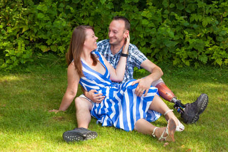 Loving couple sitting on the grass looking affectionately into each others eyes, the man wearing a prosthesis after a leg amputation
